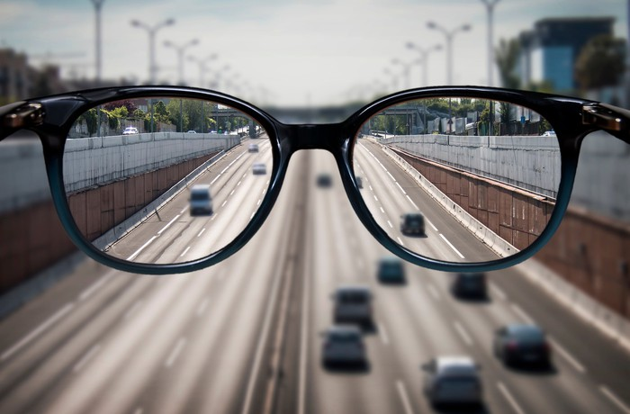 A suspended pair of eyeglasses, showing vehicles on a highway