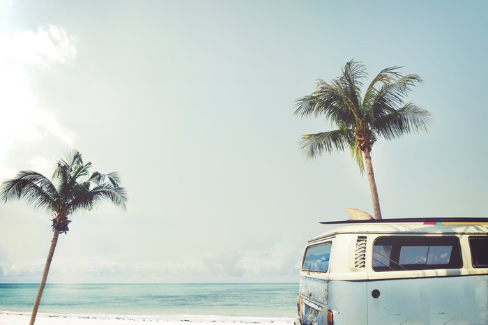 A minibus on the beach in front of two palm trees