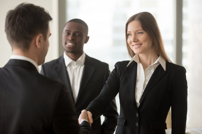 Female professional shaking hands with male professional while a second male professional looks on