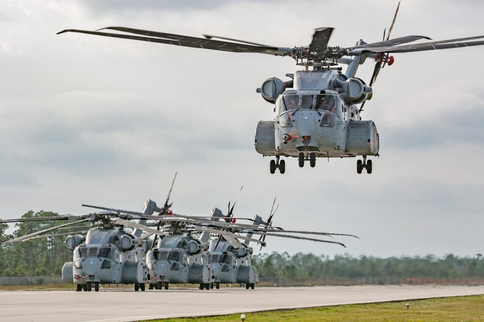 Several CH-53K helicopters, one coming in for a landing