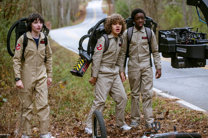 Three children dressed in Ghostbusters costumes in a scene from Stranger Things 2 in a shot from the