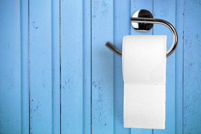 Toilet paper on holder attached to a light blue wall.
