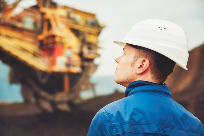 A man wearing a hard hat and looking up at mining equipment