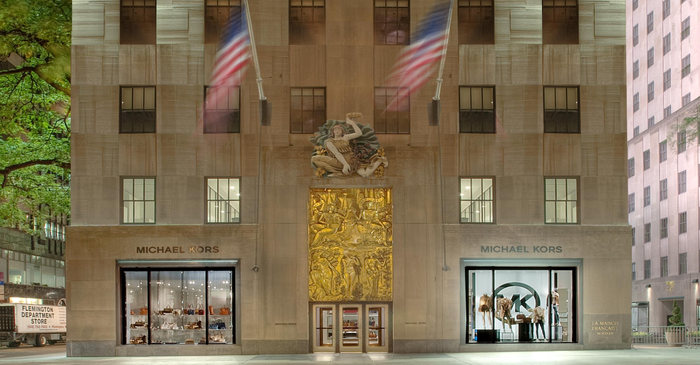 Michael Kors location at Rockefeller Center in New York, with gold art on side of building and two American flags.