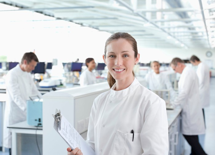 Smiling lab worker with a clipboard.
