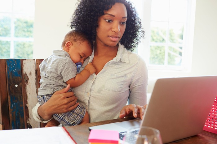 Woman holding a baby at a computer