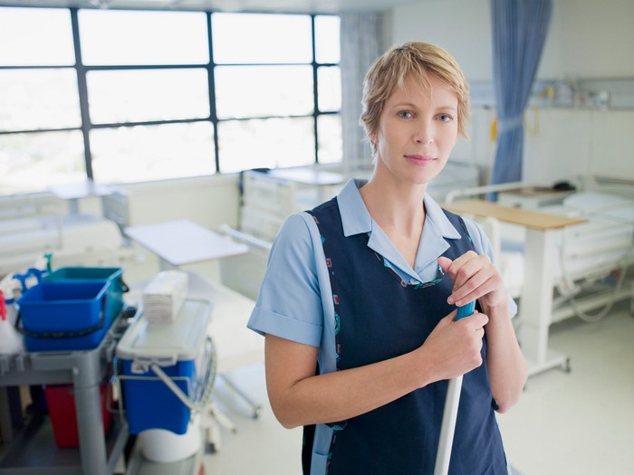 Woman janitor standing in hospital room