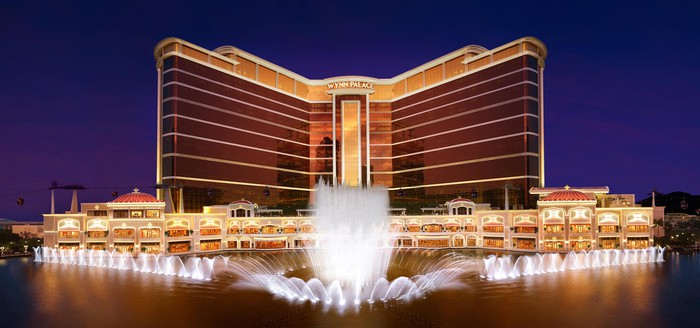 Wynn Palace casino resort in Macau, with lit-up fountains in front of the hotel.