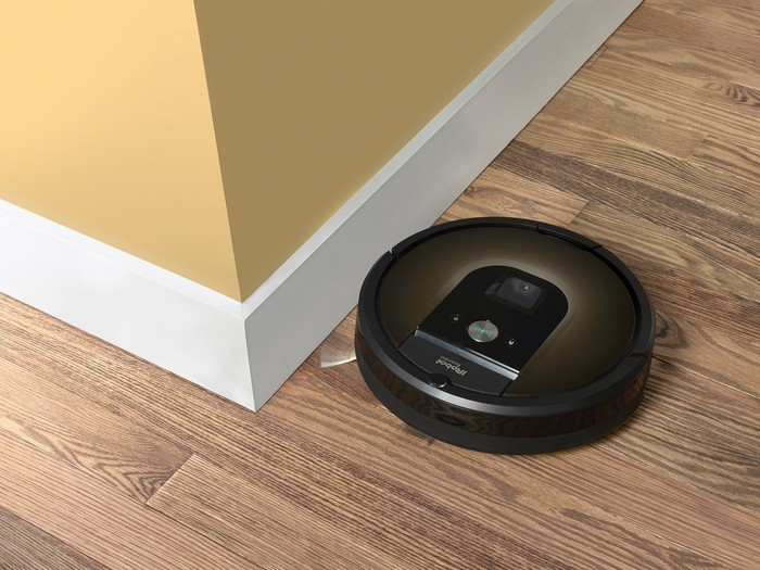 iRobot Roomba 980 rounding a corner on a hardwood floor