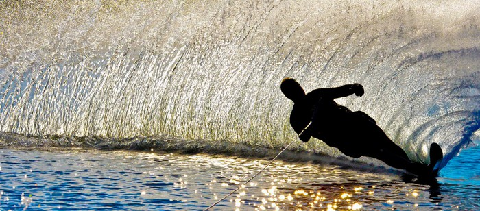 Dark silhouette of a waterskiing man taking a sharp turn.