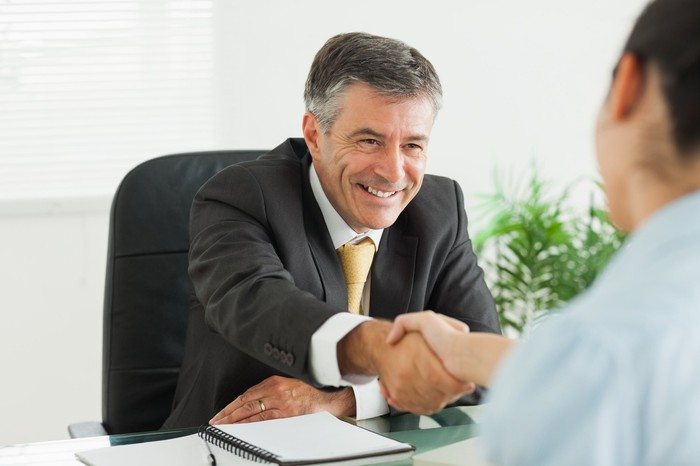 Older man in a suit shaking hands with another professional