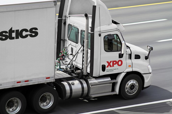 White semi tractor-trailer with XPO logo on it, driving down a four-lane highway.