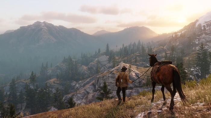 Man walking horse over beautiful, rugged terrain in screen shot from Red Dead Redemption 2.