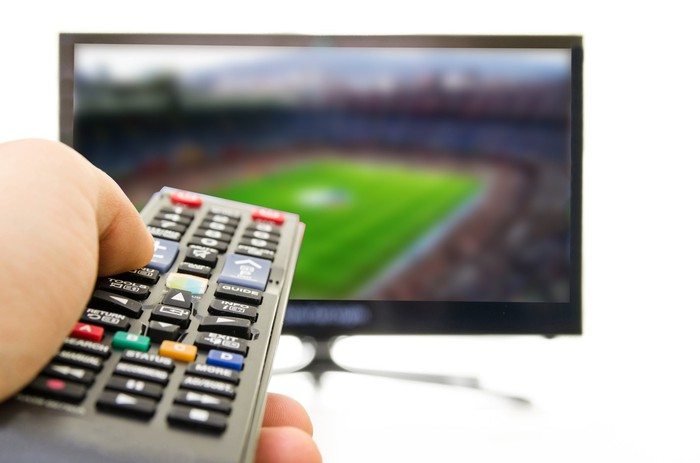 A closeup shot of someone holding a TV remote, with a TV displaying a sports game in the background.