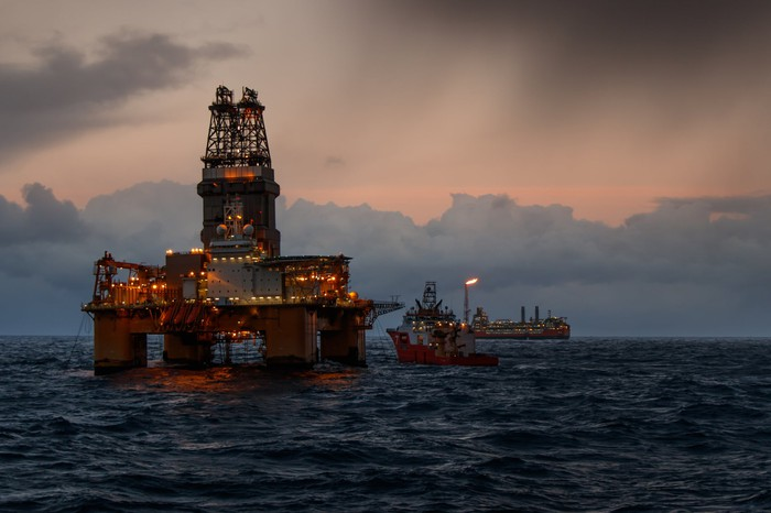 Offshore oil rig and support ship at sea.