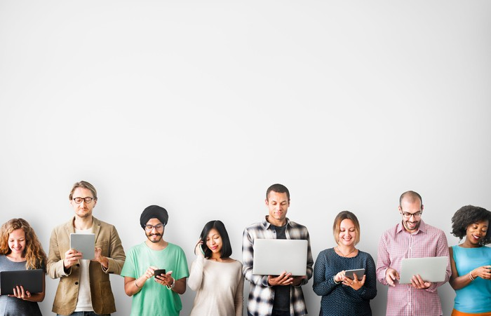 A group of people standing against a white wall using smartphones, tablets, and laptops.