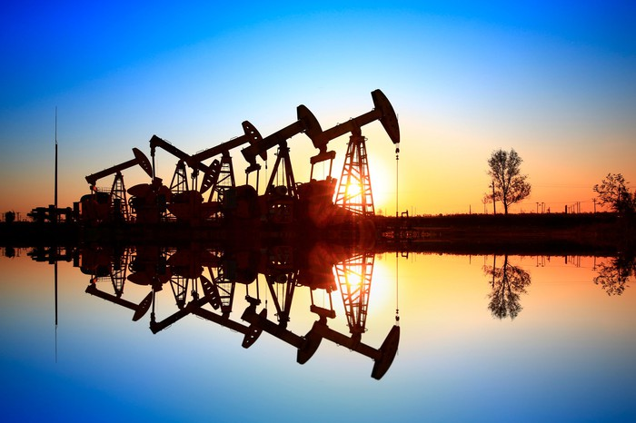 A row of oil pumps reflected on a lake at sunset