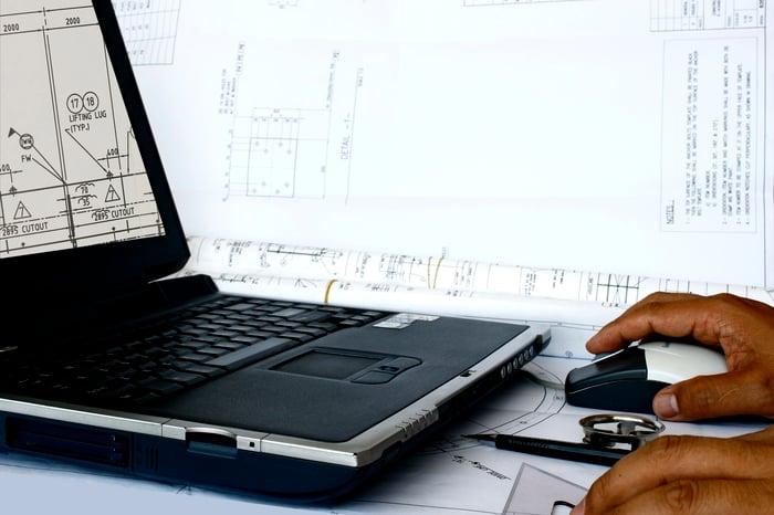 A man edits a design document on a laptop.