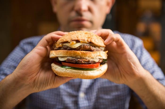A man holding up a juicy burger