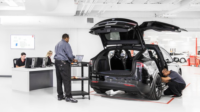 Tesla mechanics working on a Model X