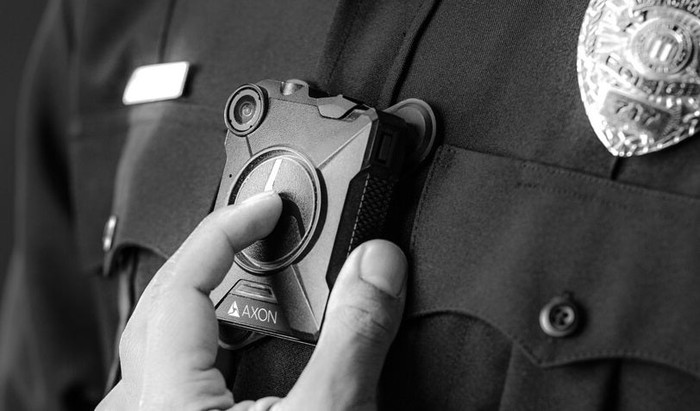 A police officer wearing an Axon body camera.