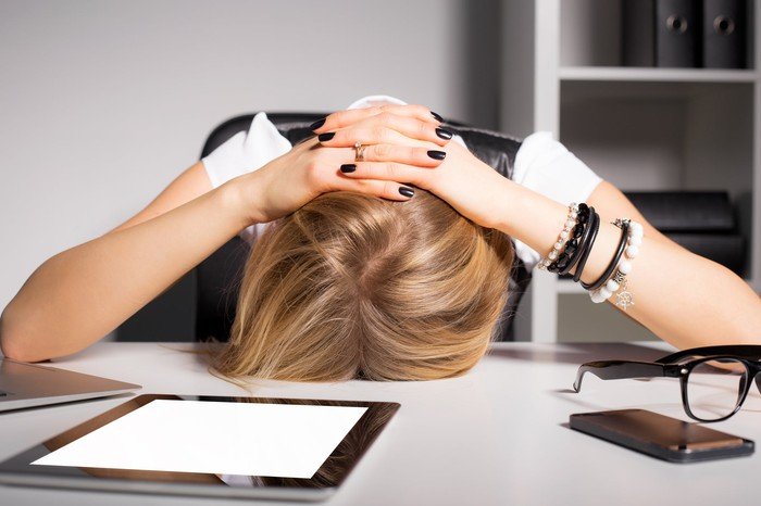 Woman putting her head down at her desk