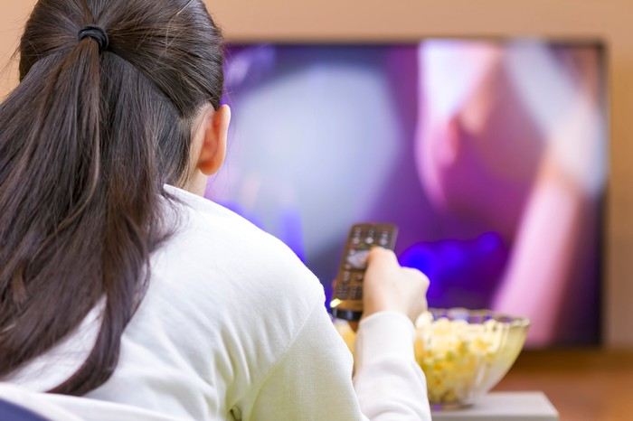 Woman watching TV eating popcorn