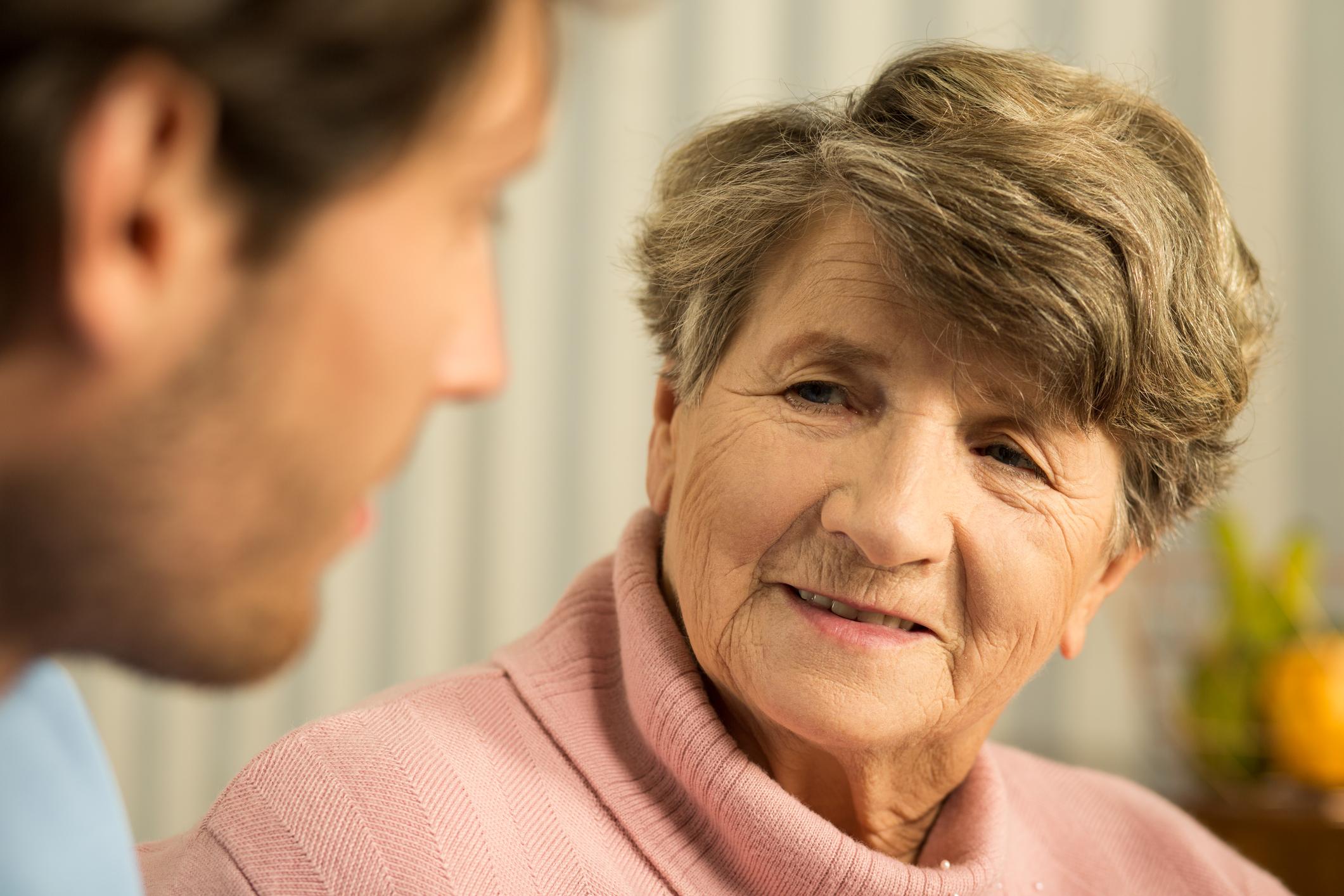 Senior woman talking to younger man