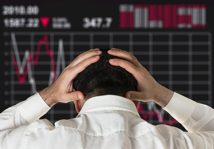 A man with his head in his hands looking at a monitor displaying a declining stock price chart.