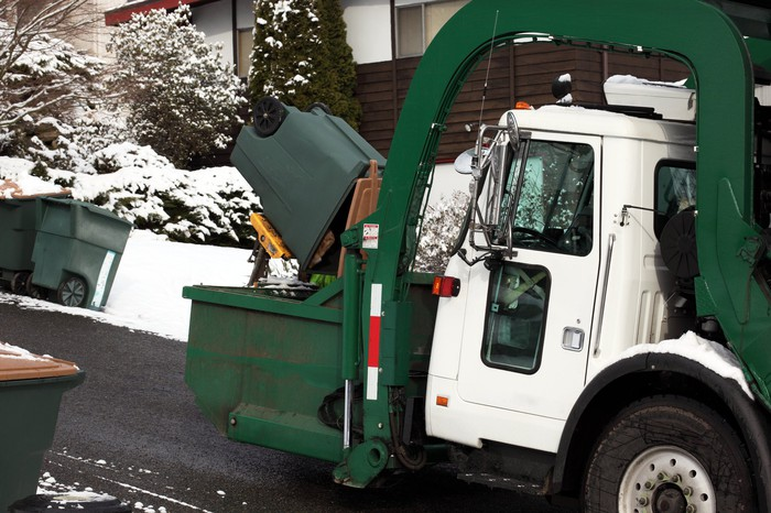 A garbage truck picking up trash in the snow.