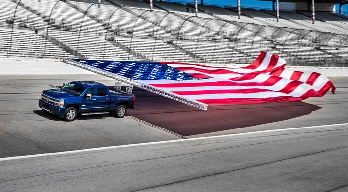 A blue Chevrolet Silverado truck hauling a large American flag on a racetrack.