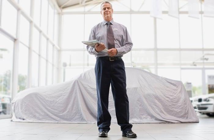 A car salesman standing in a dealership.