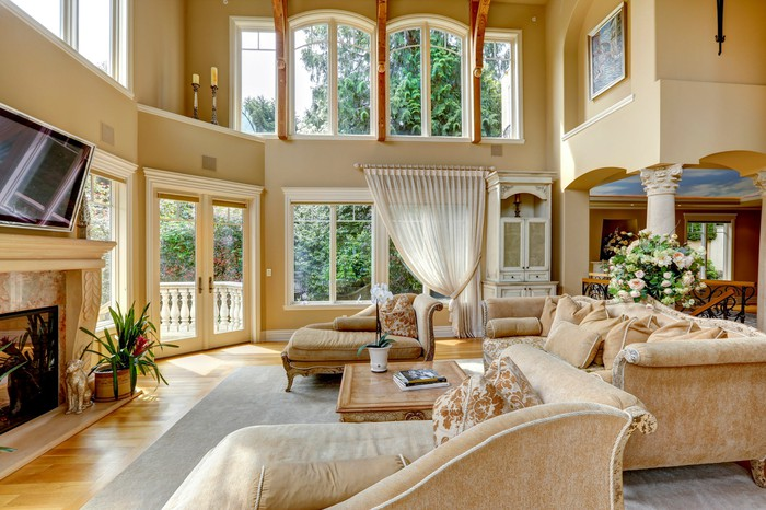 Large home interior featuring a sunlit living room with tan furniture and many windows.