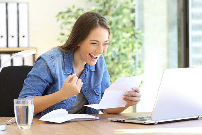 Woman looking at a piece of paper with a happy expression on her face
