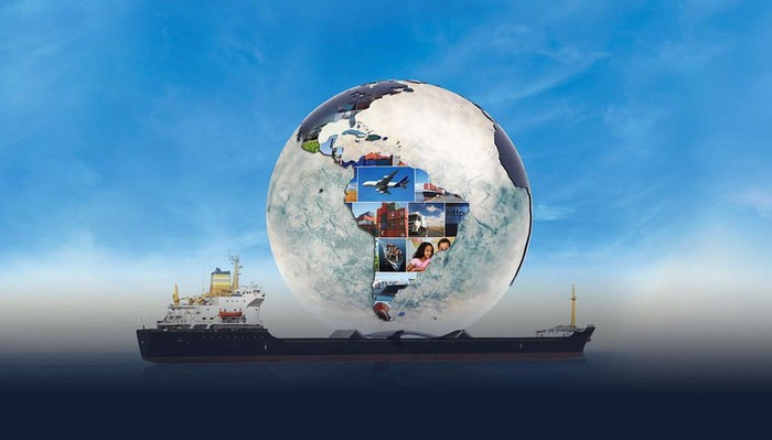 Glass globe resting on a cargo ship at sea with a blue sky, with globe showing South America and pictures of various activities.