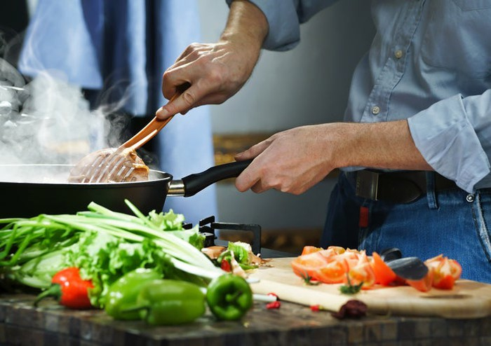 A chef prepares hotpot items on a stove top frying pan at home, with various vegetables on a chopping board on top of the stove.