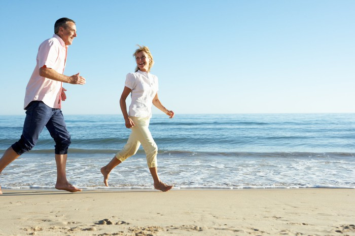 Mid-aged couple running along the beach