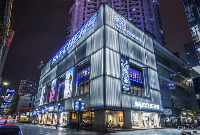 A new ultra-modern Skechers storefront in China. The building is surrounded by high rises, and has metal sheeting exterior.