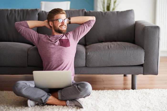 A smiling, bespectacled man sitting on the floor with leg crossed, arms up behind his head, and a laptop on his lap