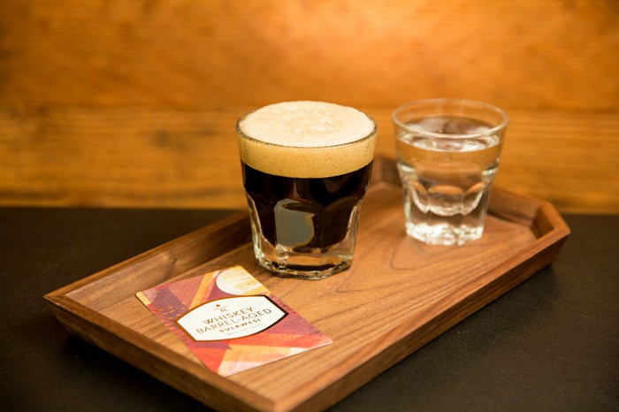 A glass of coffee is on a wooden board next to a glass of water.