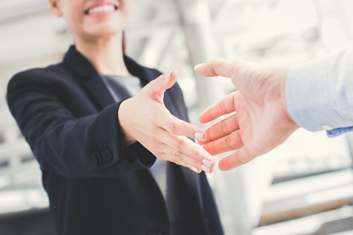Businesswoman holds out her hand for a handshake.
