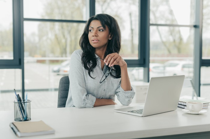 Businesswoman sits at a desk looking pensive.