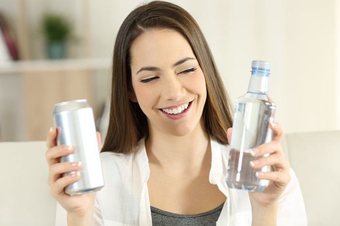 A smiling young woman chooses between water in a can or a bottle, both unbranded.
