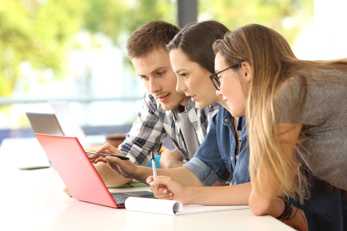 Three students looking at the same laptop screen.