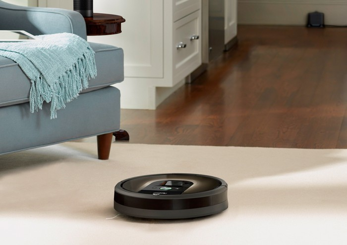 A Roomba robotic vacuum near a light blue armchair or sofa on a white rug that's covering part of a hardwood-floored room.