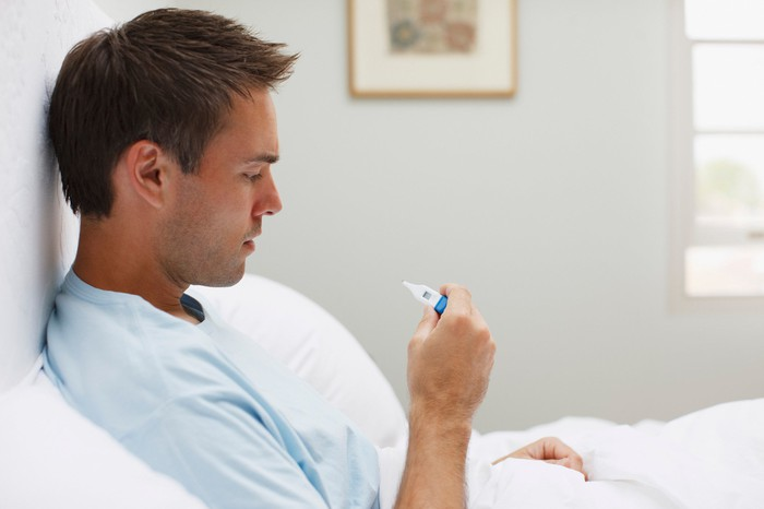 A man in bed looking at a thermometer