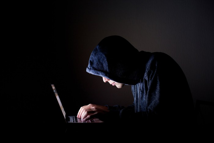 A hacker in a dark room hunched over a laptop with the glow of the screen highlighting his fingers and dark hoodie.