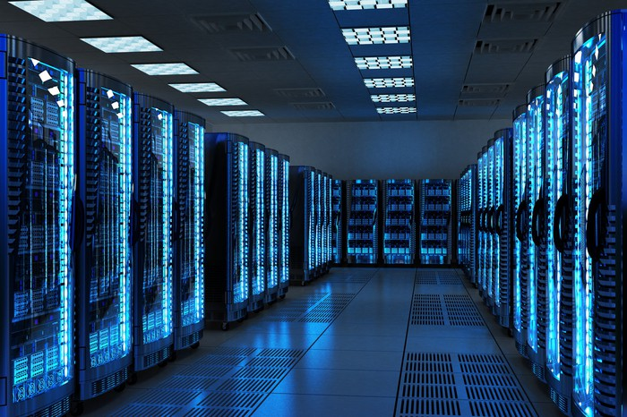 Interior of a blue-lighted data center showing servers along both sides and at the end of an aisle.