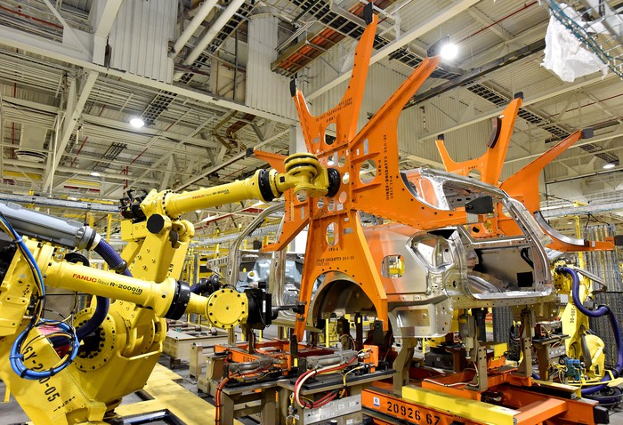 A scene from the assembly line: Two large yellow robots are putting body panels on an SUV's frame.