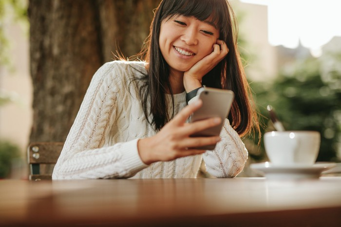 Chinese girl sitting at a table with a teacup in front of her, smiling at a smartphone
